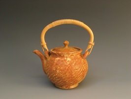 This teapot by potter Cliff Glover is textured with a rope and glazed with a matt glaze the color of rust.