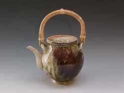 This teapot by ceramic artist Cliff Glover features a Shino glaze with a heavy application of wood ash which helps attach any fugitive copper thus creating a red